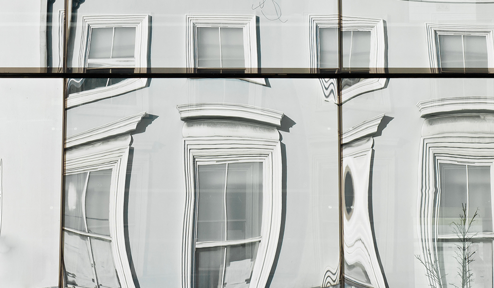 A row of townhouses reflected in glass panels