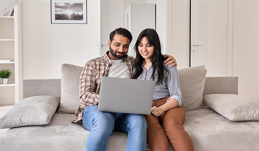 Happy family couple using laptop looking at computer sitting on sofa together